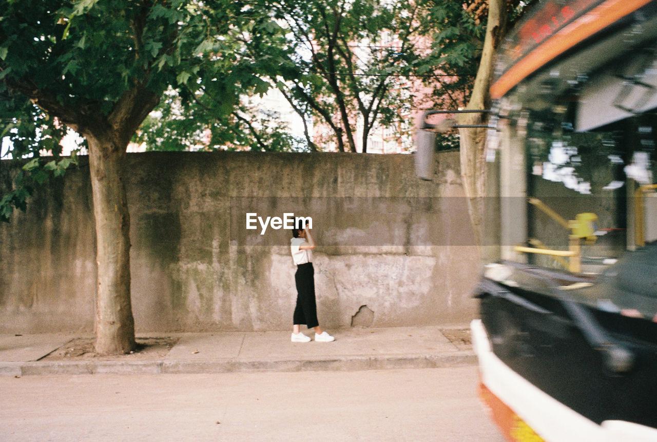 Side view of woman walking on sidewalk in city