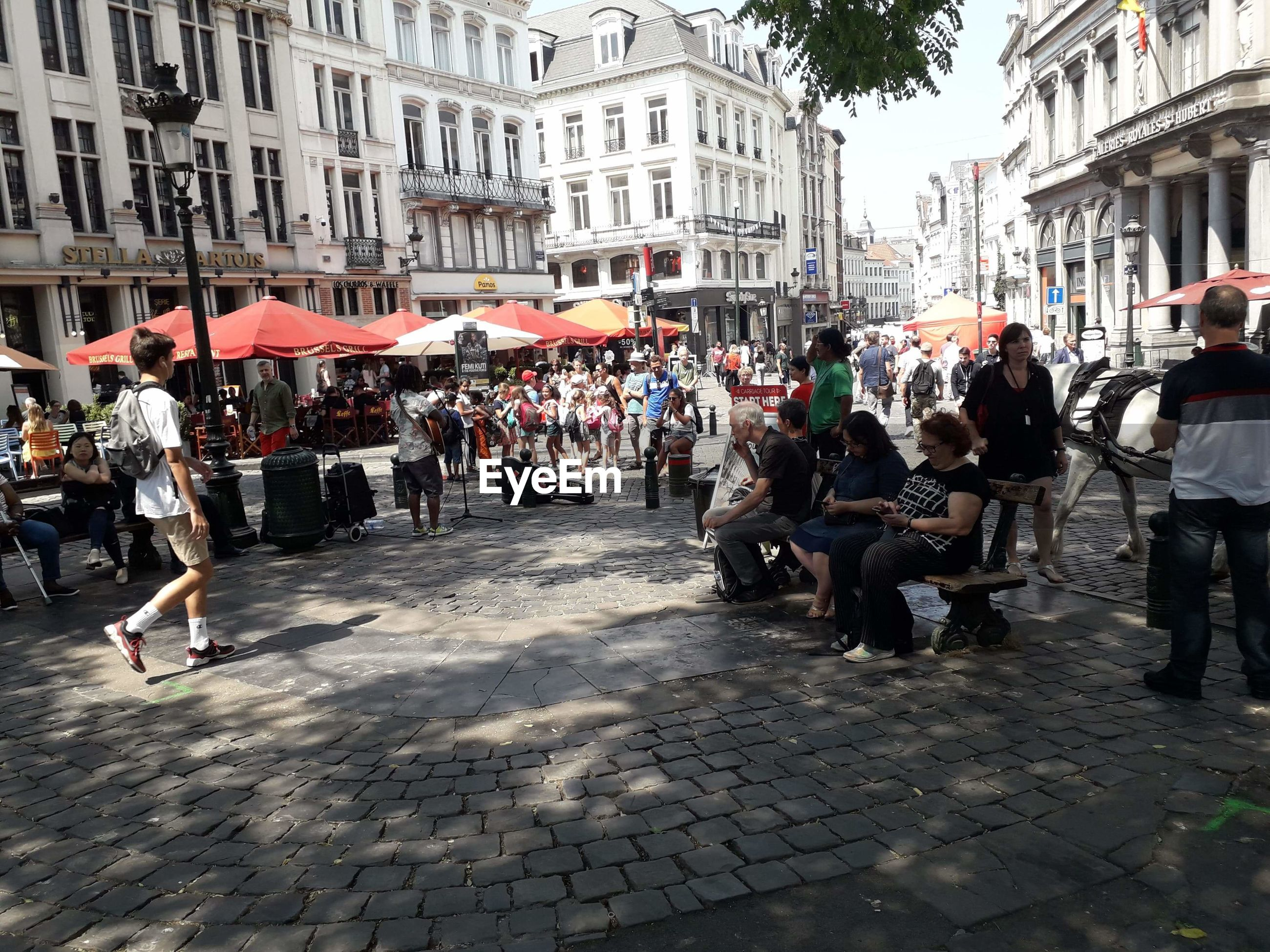 group of people, city, building exterior, architecture, large group of people, crowd, real people, built structure, street, men, women, adult, city life, day, lifestyles, building, cobblestone, city street, transportation, outdoors, paving stone