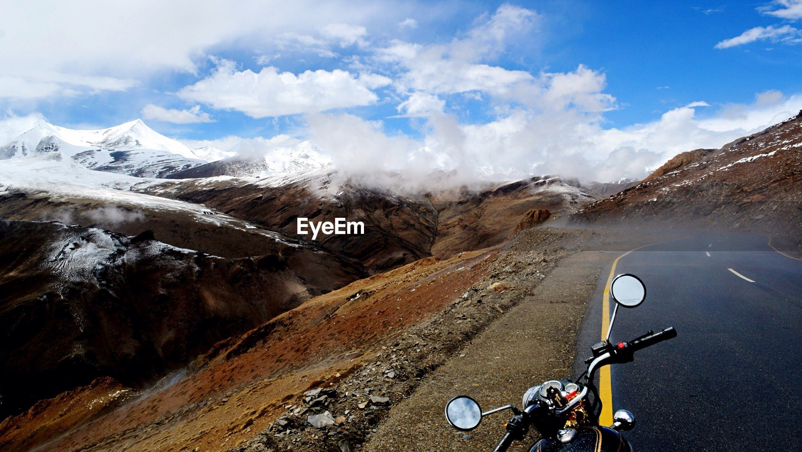 High angle view of motorcycle on street against mountains and cloudy sky