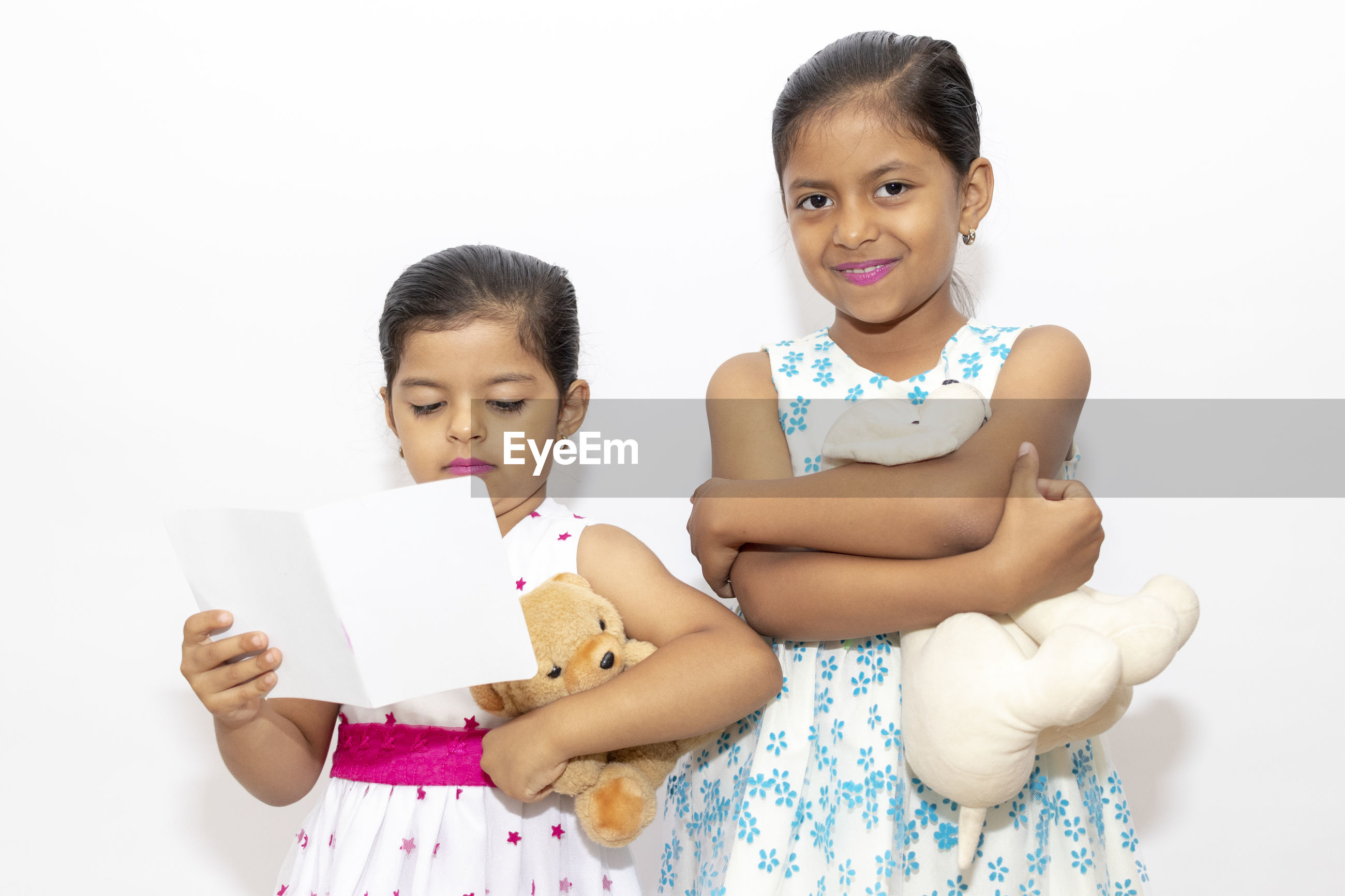 Front view of smiling girls with toy against white background
