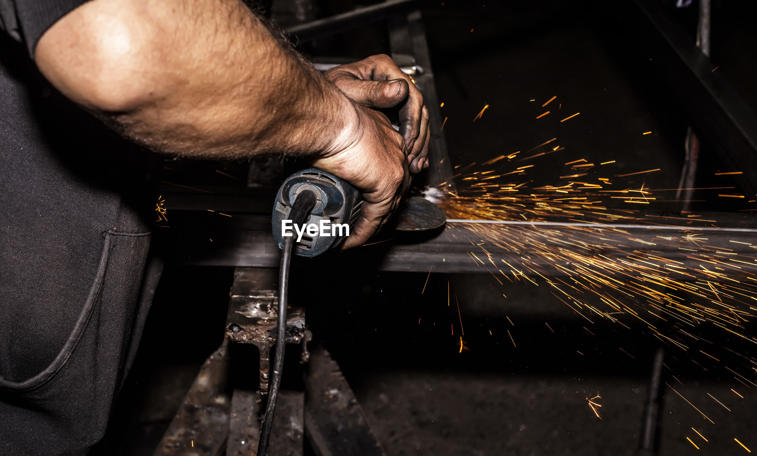 Midsection of welder working in factory