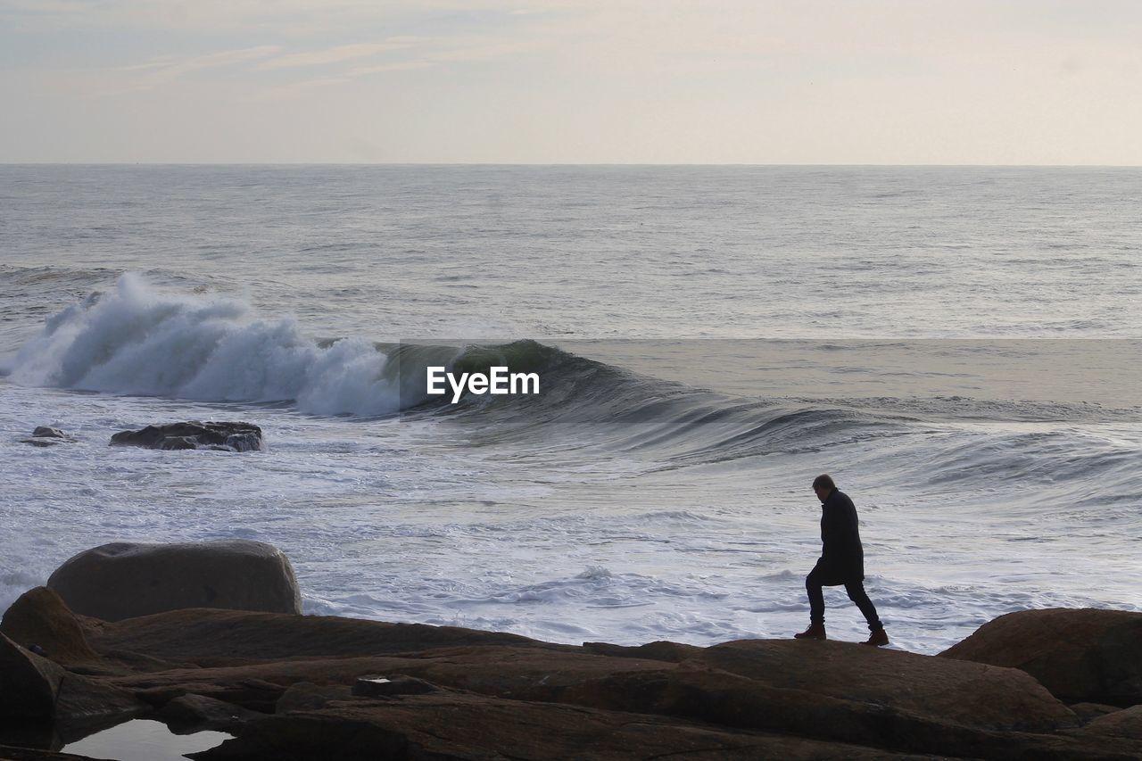 Man walking on rocks by sea against sky
