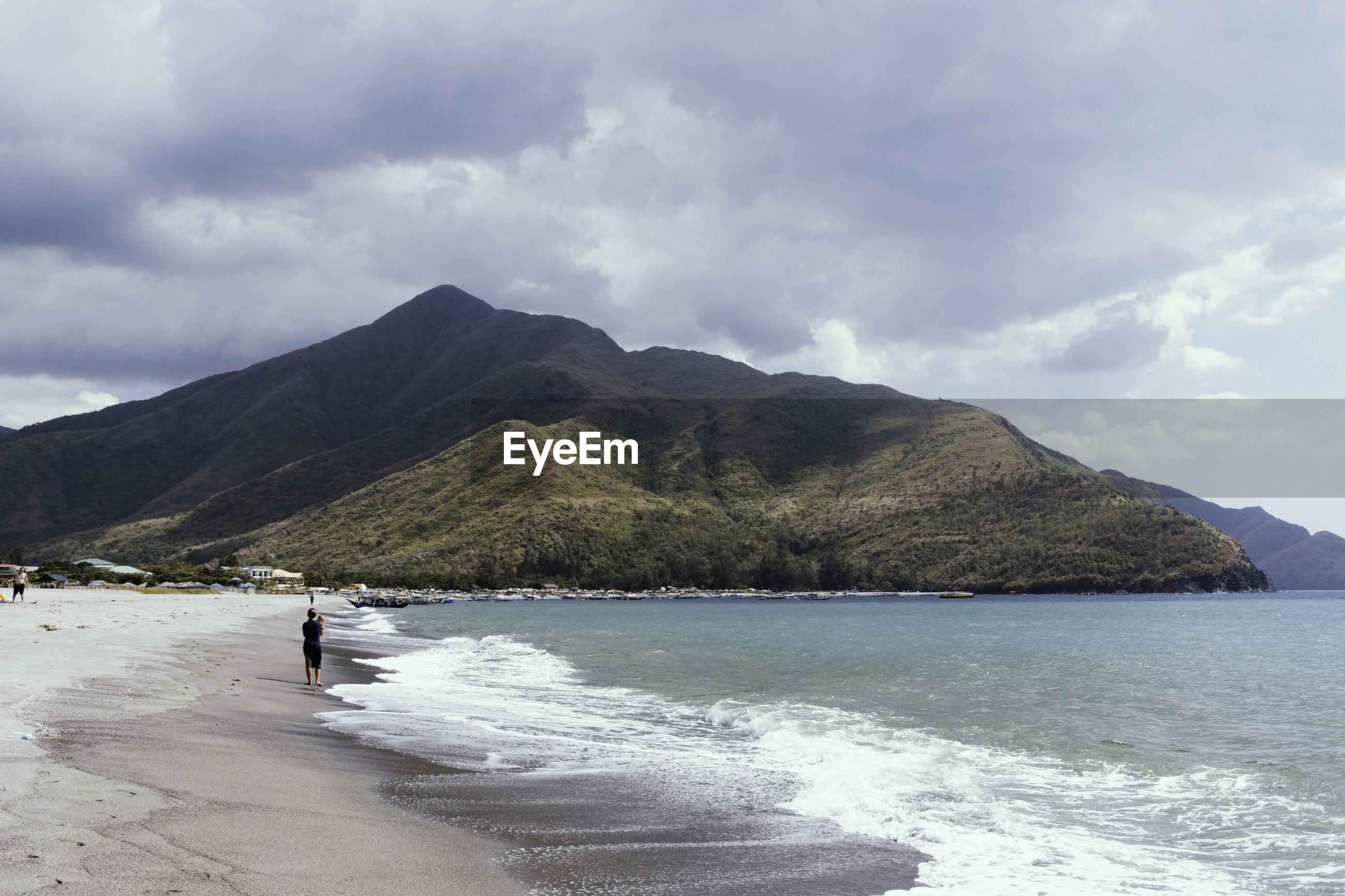 Man at beach against sky