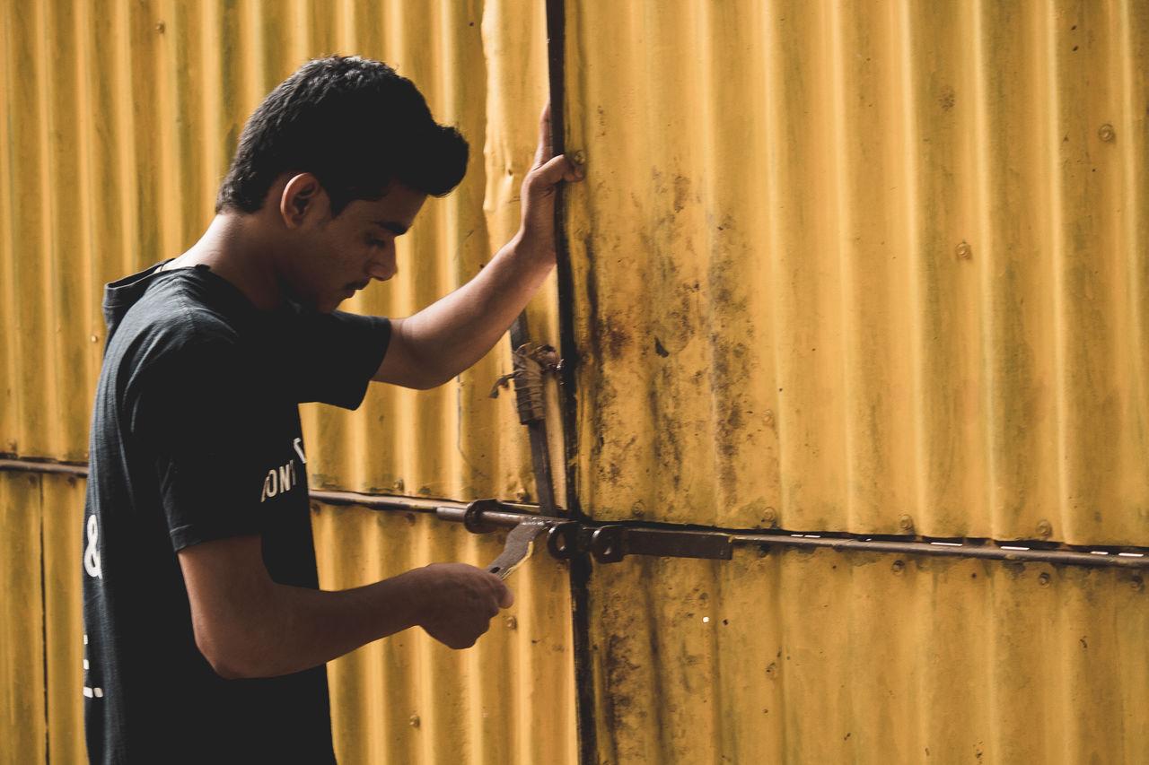 Boy Standing Against Rusty Door