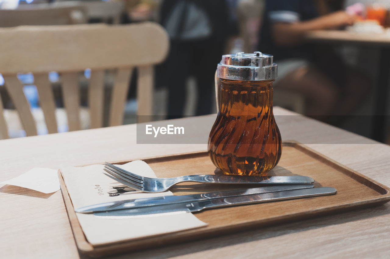 Close-up of honey with cutleries on wooden table