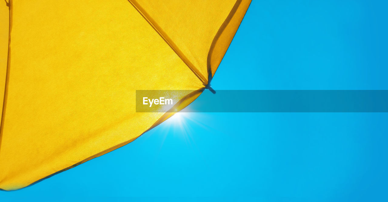 yellow, blue, sky, umbrella, copy space, no people, clear sky, protection, security, parasol, textile, low angle view, sunshade, shade, nature, day, single object, close-up, beach umbrella, outdoors