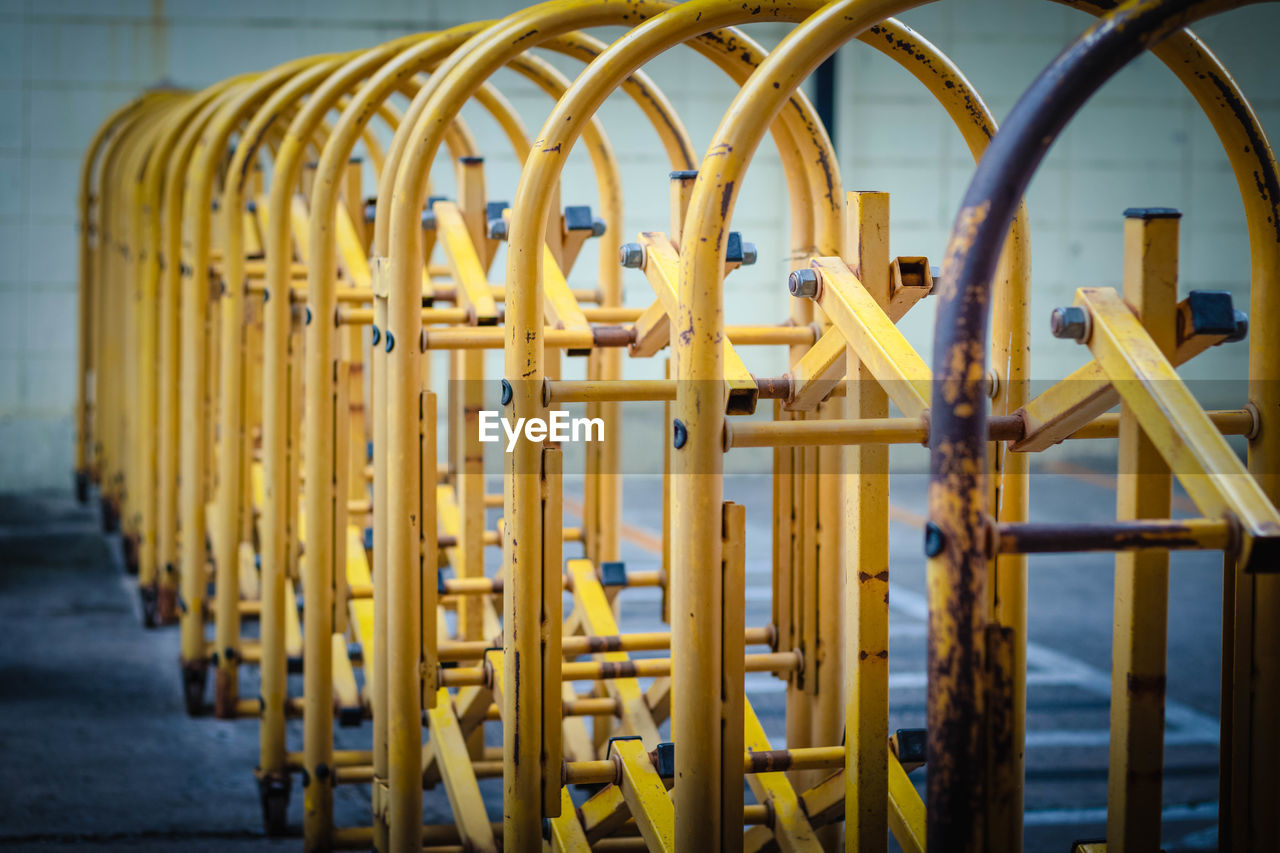 yellow, metal, no people, in a row, focus on foreground, day, selective focus, industry, repetition, outdoors, absence, technology, close-up, safety, control, barrier, pattern, wood - material, built structure, factory, outdoor play equipment