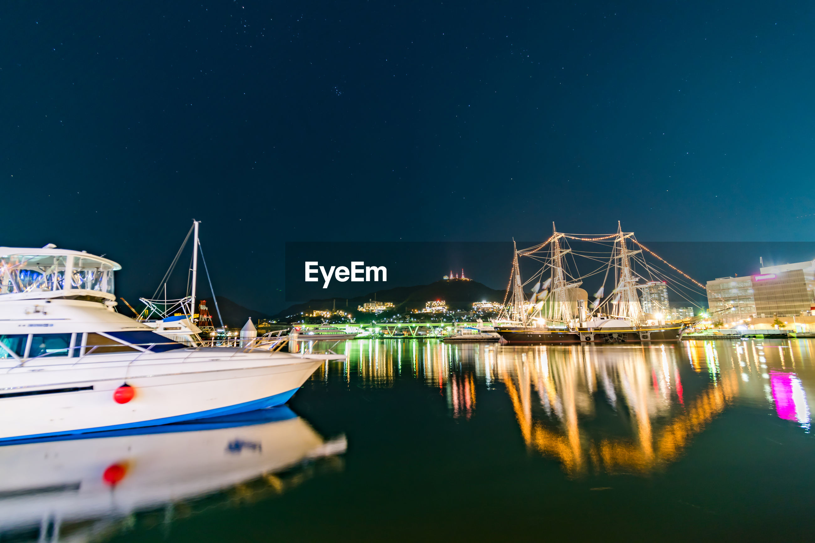 BOATS MOORED ON RIVER AGAINST ILLUMINATED SKY