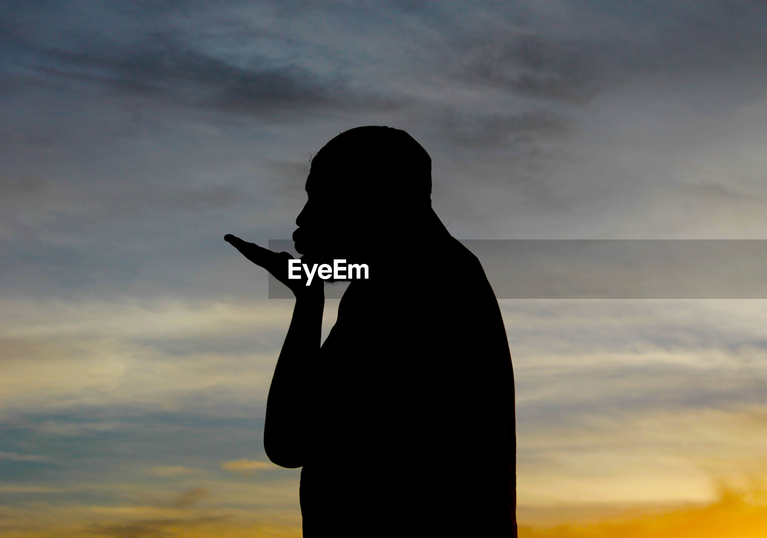 Silhouette of a man against cloudy sky at sunset