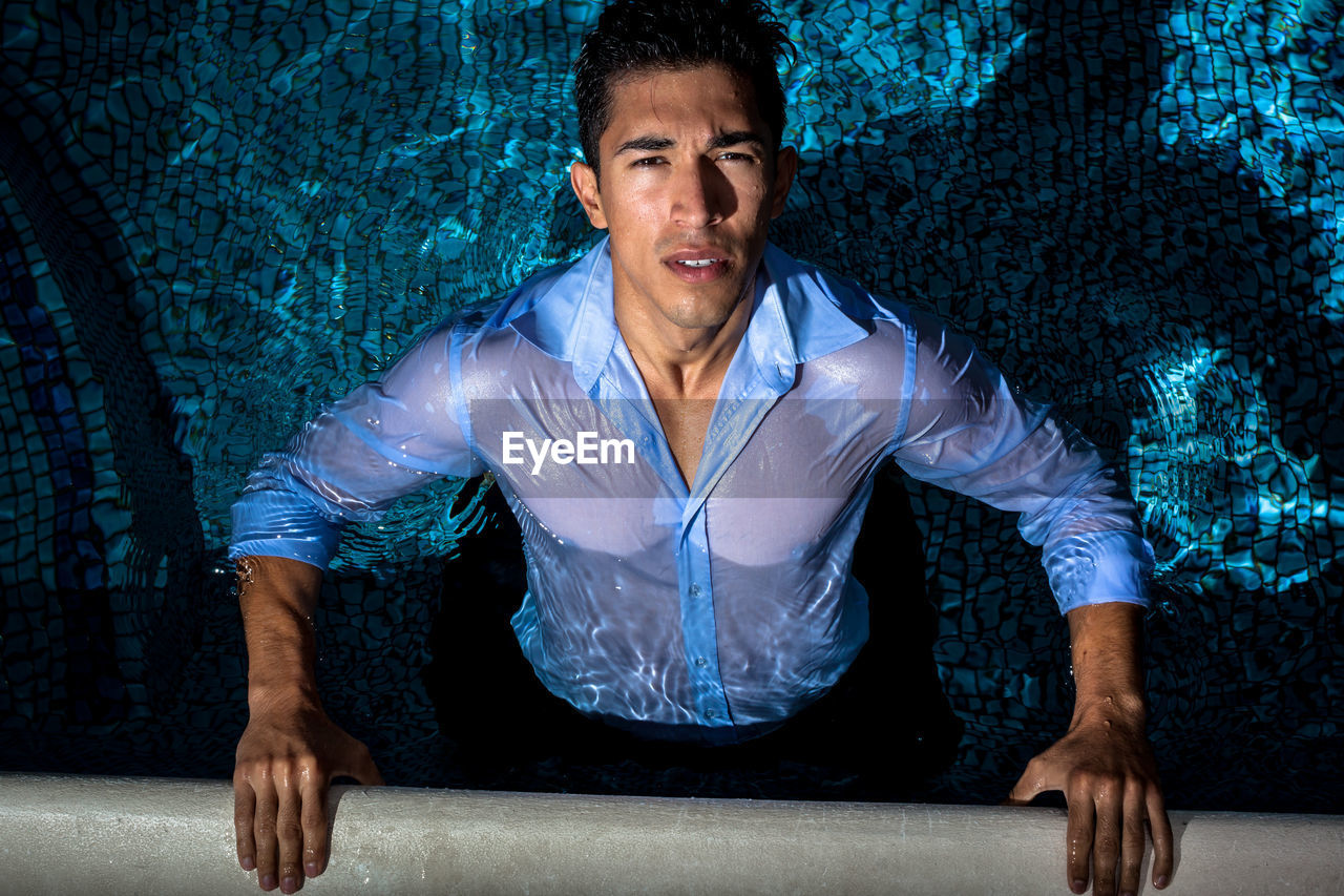 High angle portrait of young man swimming in pool