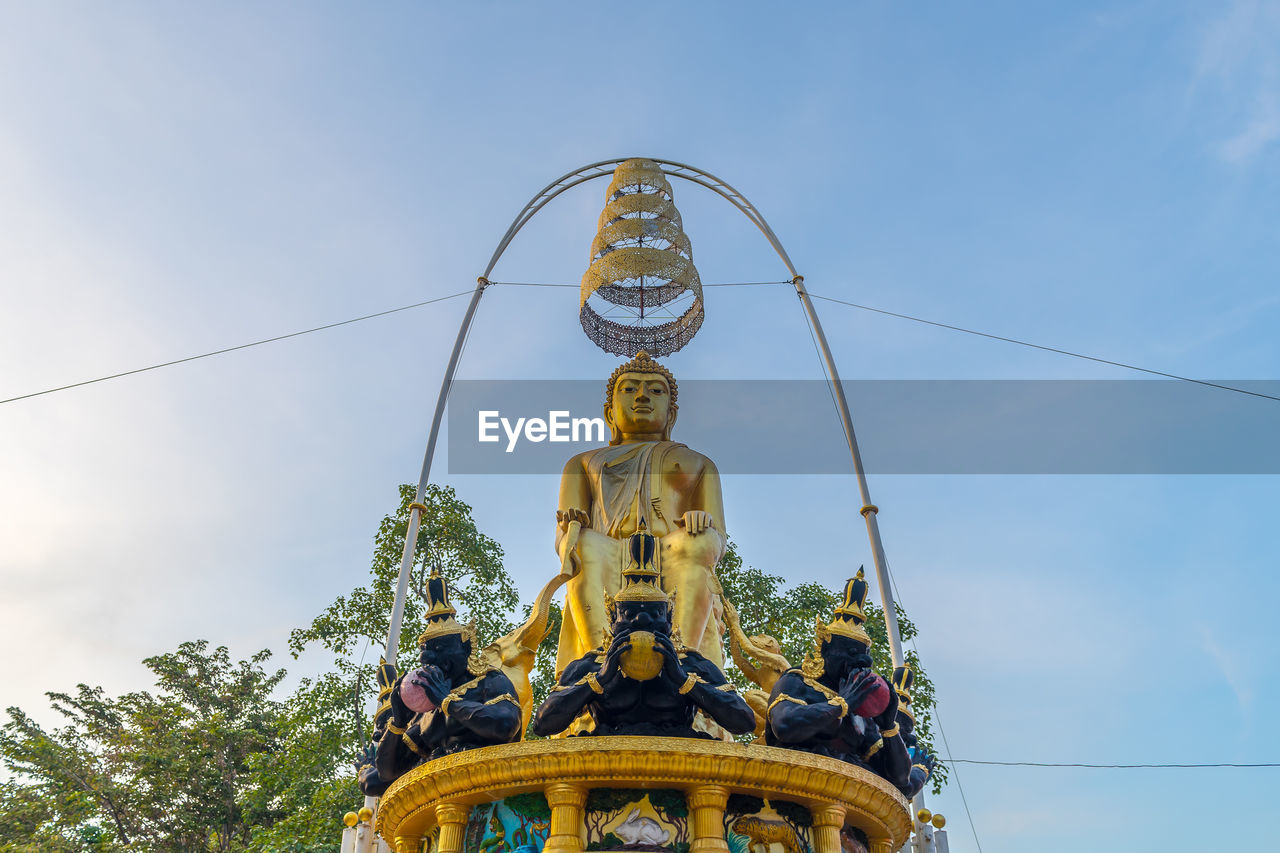 sky, low angle view, sculpture, representation, belief, religion, human representation, spirituality, statue, art and craft, nature, day, gold colored, place of worship, built structure, no people, male likeness, outdoors, cloud - sky, blue, idol
