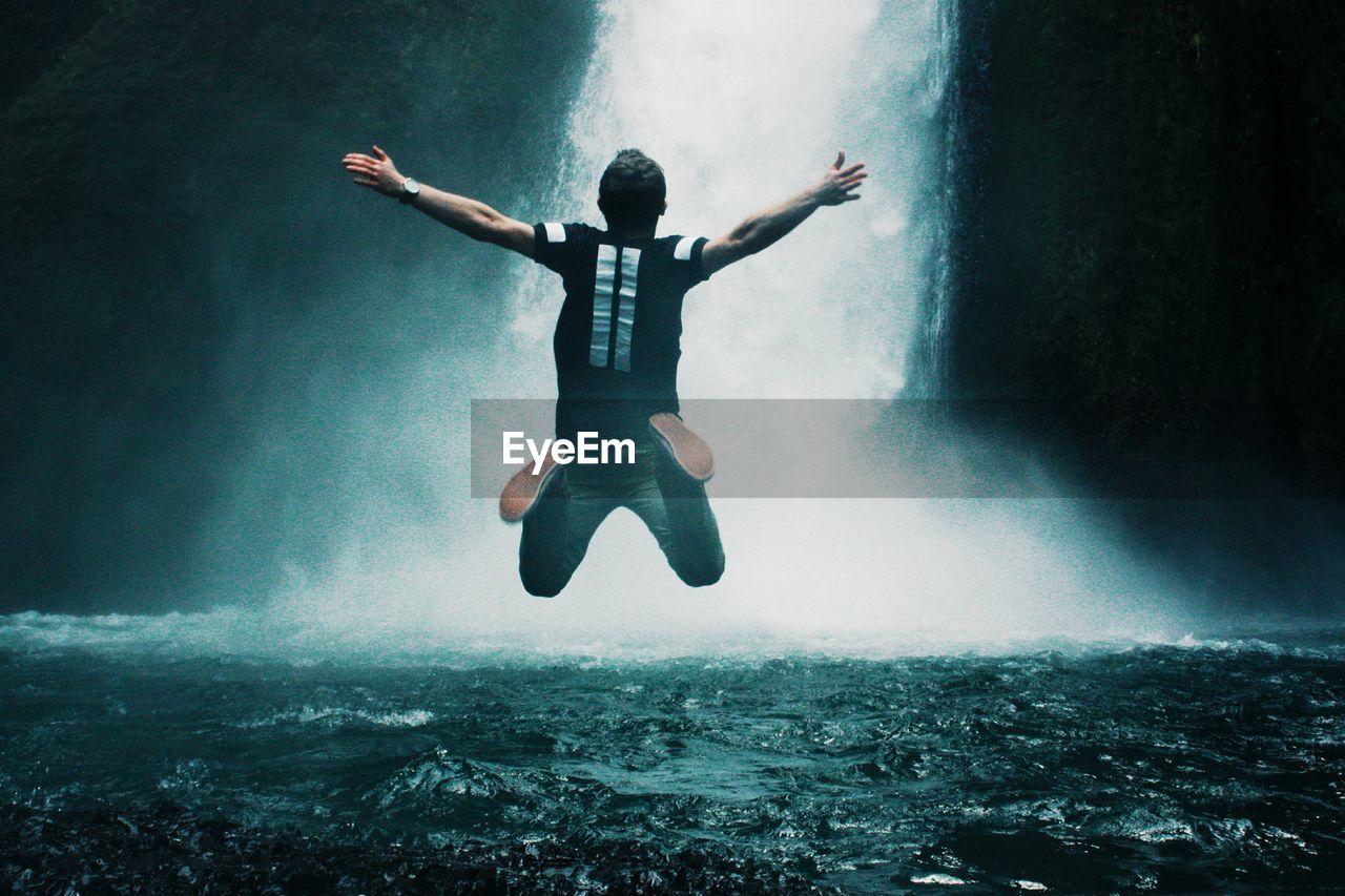 Man Jumping In Waterfall