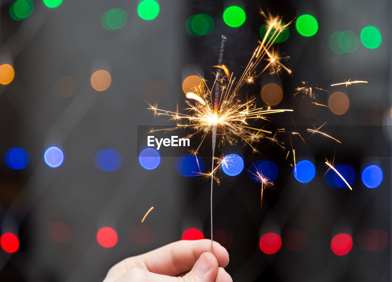 Close-up of person holding sparkler against illuminated background