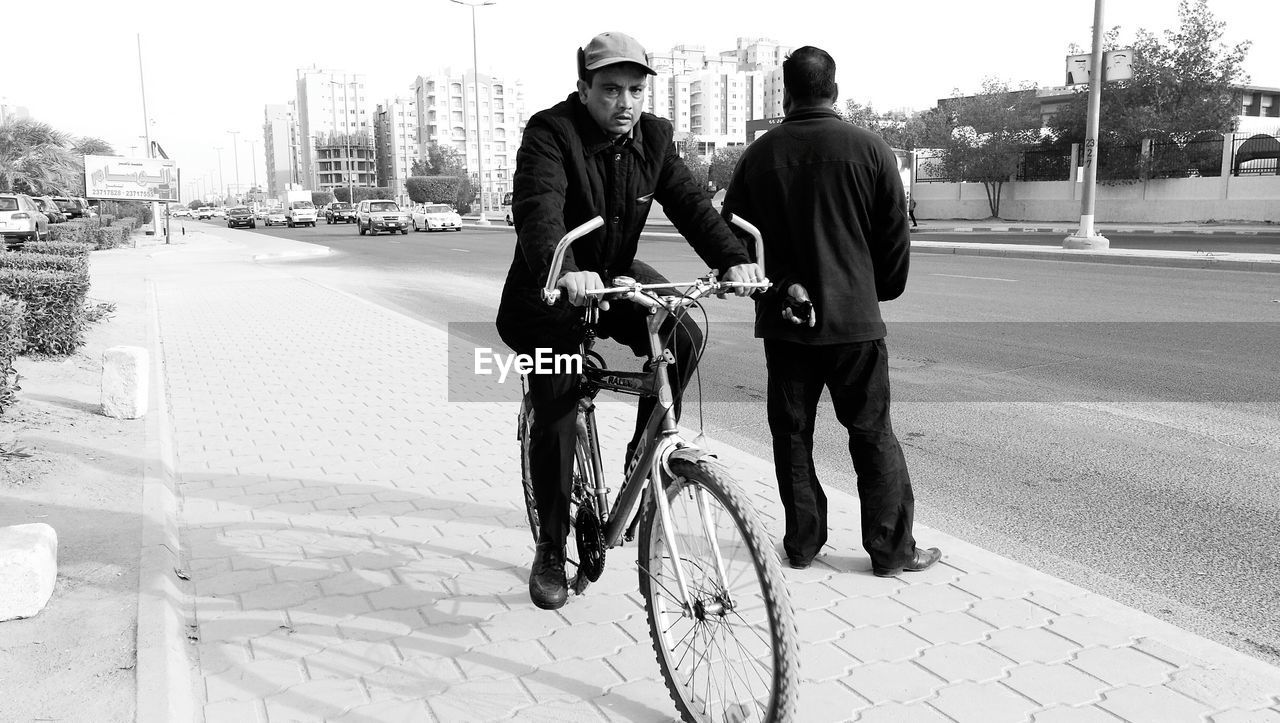 full length, bicycle, real people, transportation, city, two people, outdoors, street, day, city life, helmet, building exterior, casual clothing, land vehicle, road, riding, men, togetherness, lifestyles, built structure, headwear, architecture, friendship, young adult, adult, people, adults only