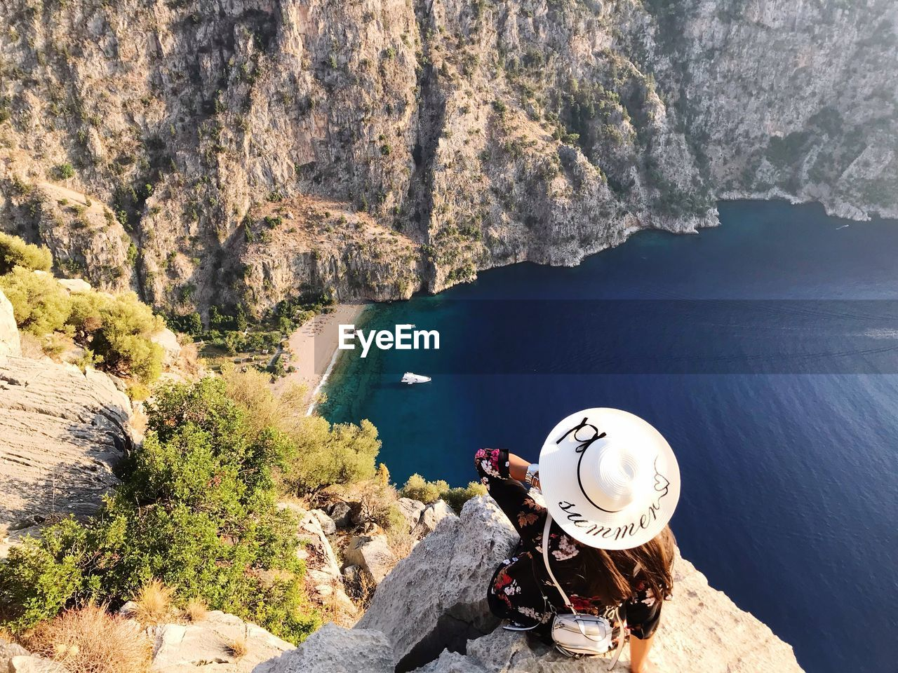 High Angle View Of Woman Wearing Hat On Cliff Over Sea