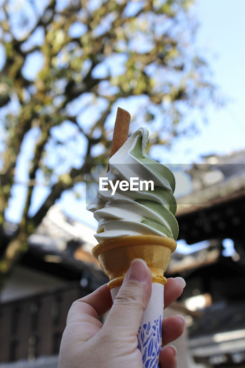 sweet food, human hand, ice cream, hand, frozen food, sweet, frozen, human body part, food and drink, holding, one person, dessert, indulgence, focus on foreground, food, unhealthy eating, temptation, dairy product, ice cream cone, real people, body part, finger, outdoors, frozen sweet food, vanilla ice cream