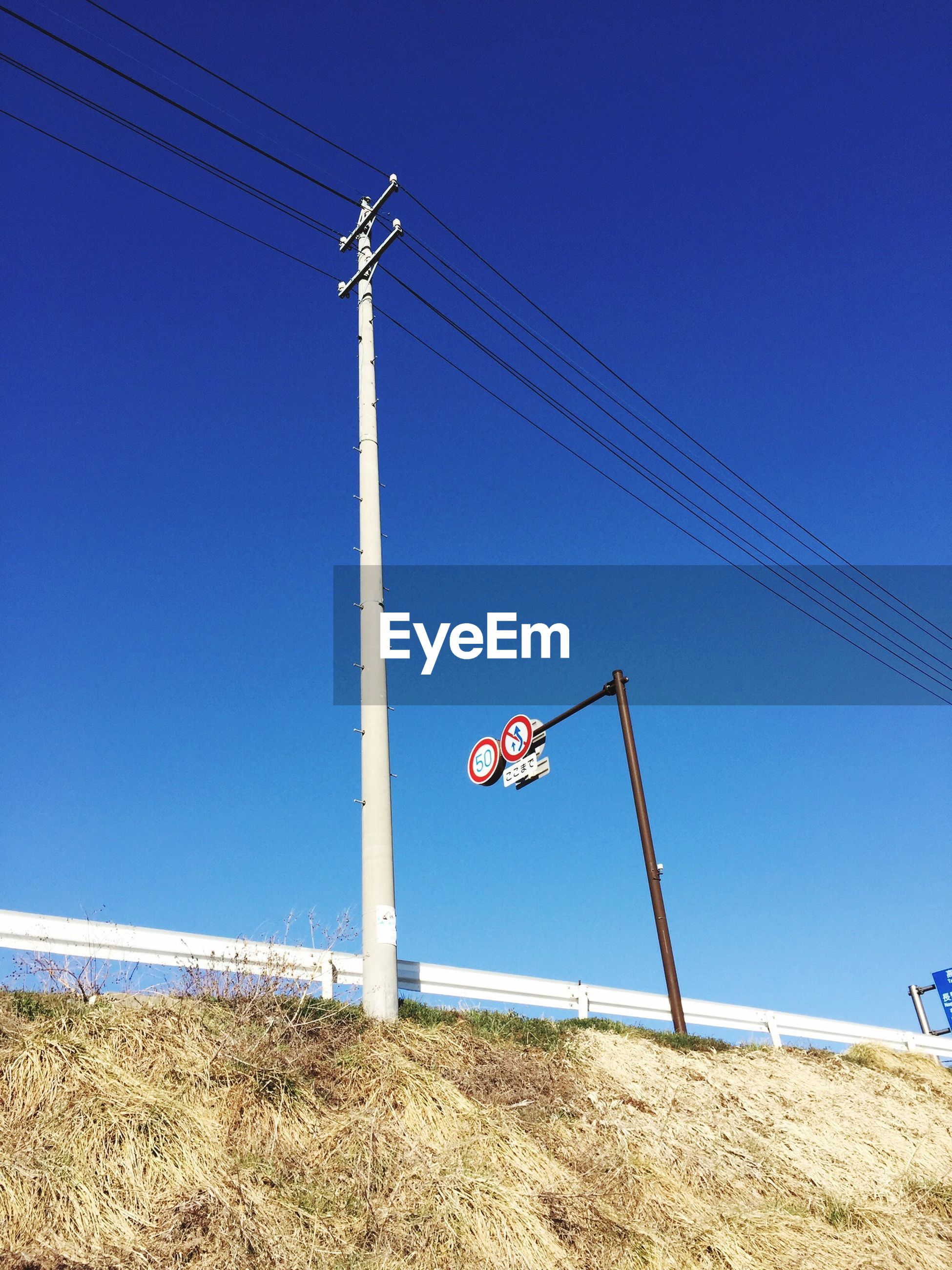 clear sky, blue, fuel and power generation, copy space, low angle view, power line, technology, cable, transportation, power supply, day, electricity pylon, electricity, environmental conservation, wind power, windmill, alternative energy, sunlight, pole, wind turbine