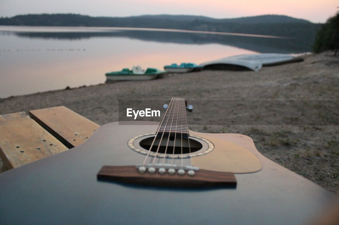 Close-Up Of Guitar At Beach At Dusk