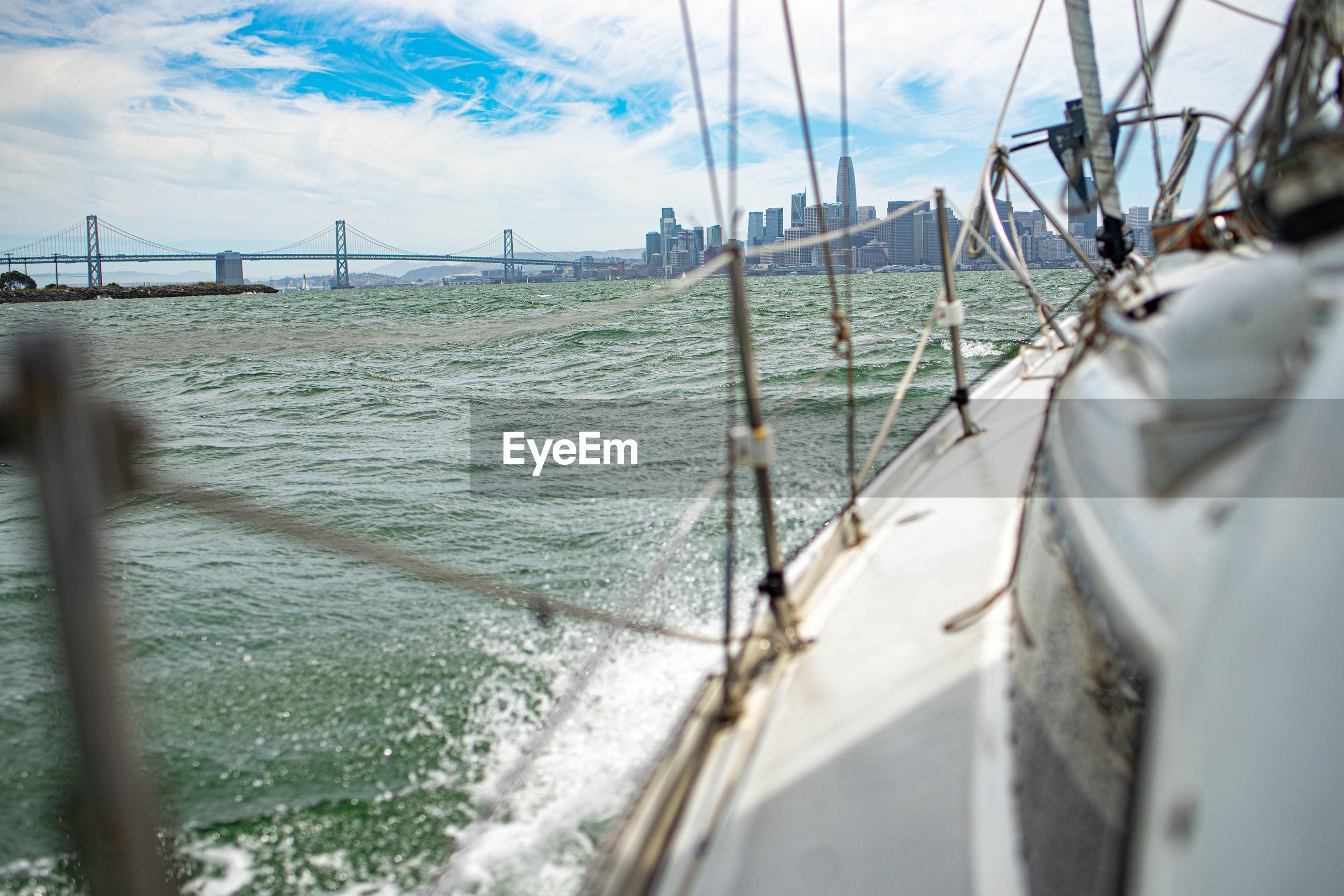 Sailboat sailing in sea against cityscape
