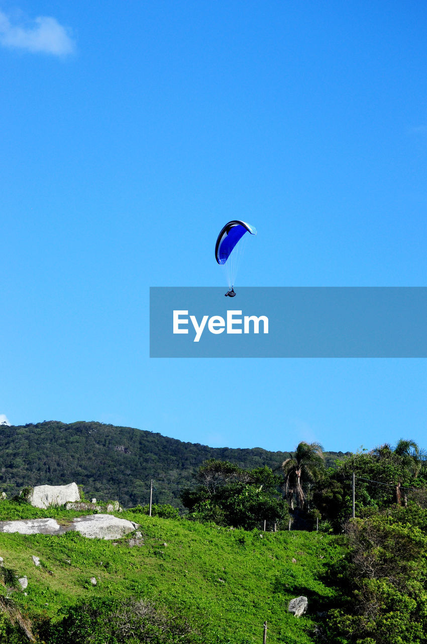 sky, adventure, extreme sports, sport, parachute, clear sky, paragliding, mountain, mid-air, environment, day, plant, blue, unrecognizable person, copy space, leisure activity, beauty in nature, flying, nature, land, freedom, outdoors
