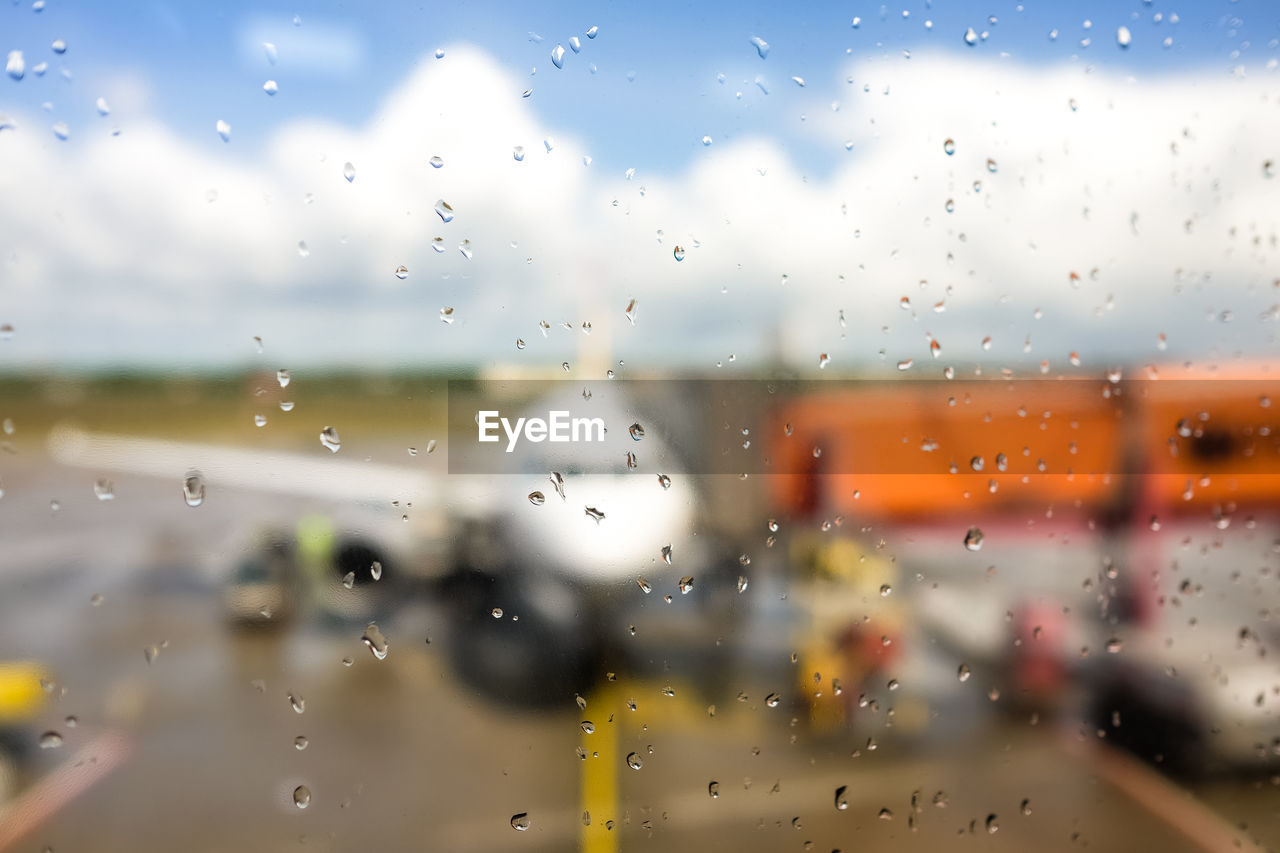 Raindrops on glass window against airplane at airport runway