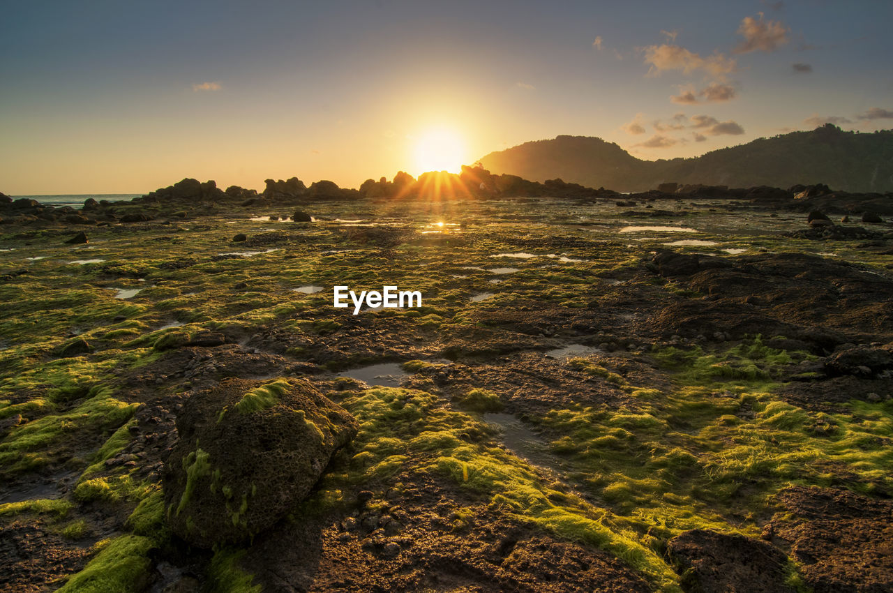 sunset, sky, beauty in nature, scenics - nature, tranquility, tranquil scene, nature, sun, sunlight, water, no people, idyllic, environment, non-urban scene, mountain, rock, land, landscape, sunbeam, lens flare, outdoors, bright