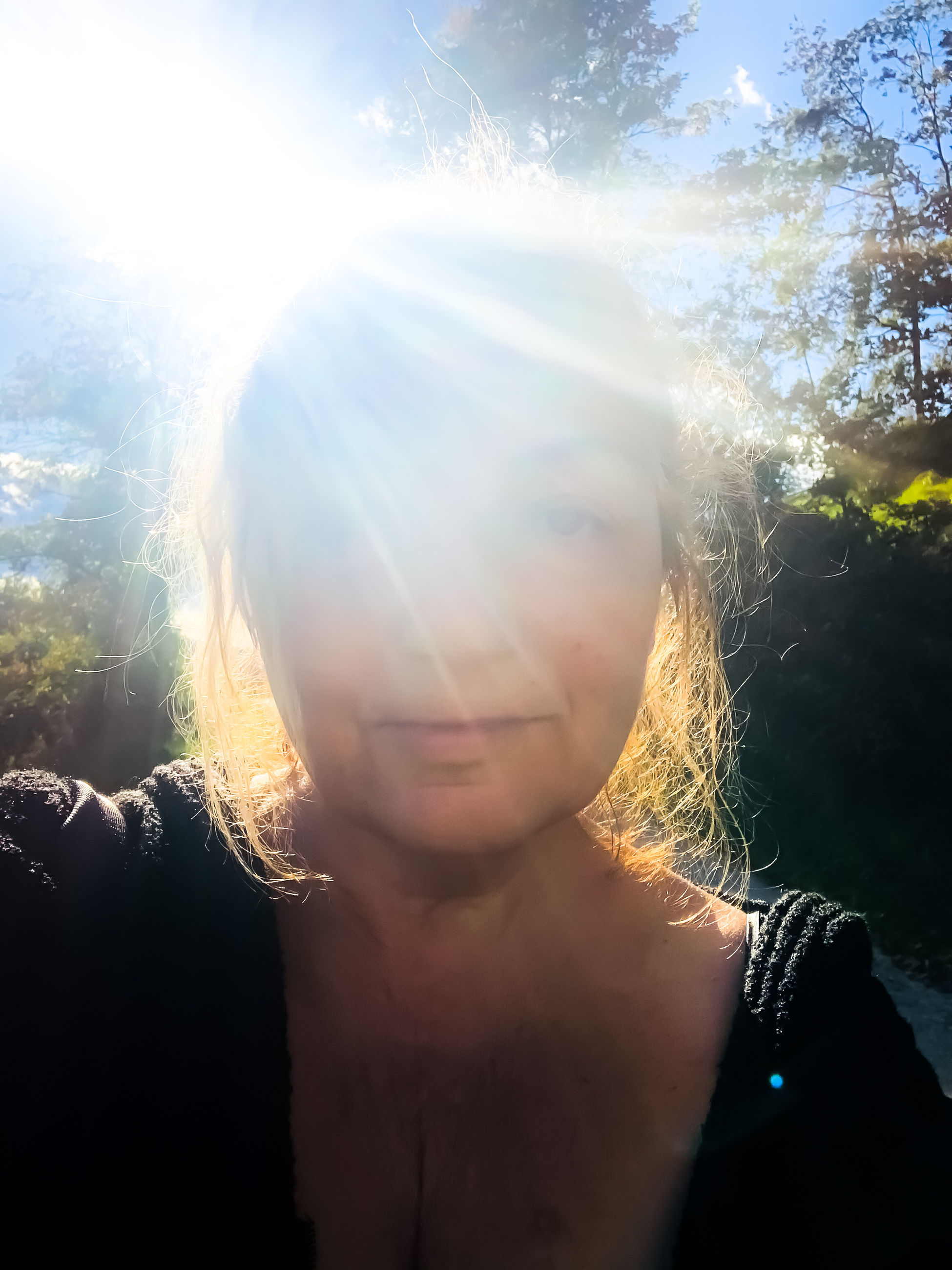 PORTRAIT OF YOUNG WOMAN AGAINST BRIGHT SUN