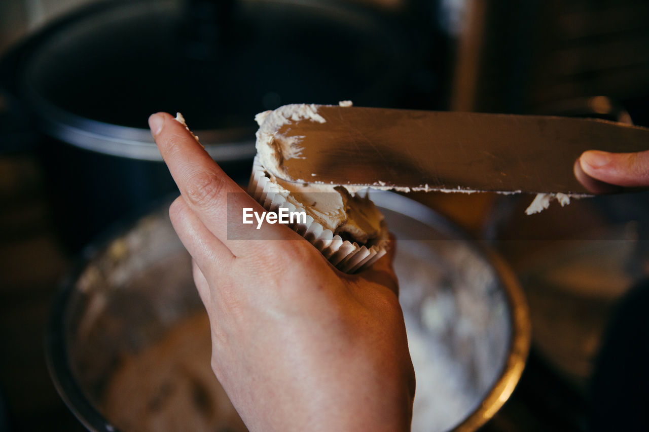 Cropped Image Of Hand Filling Icing In Cupcake