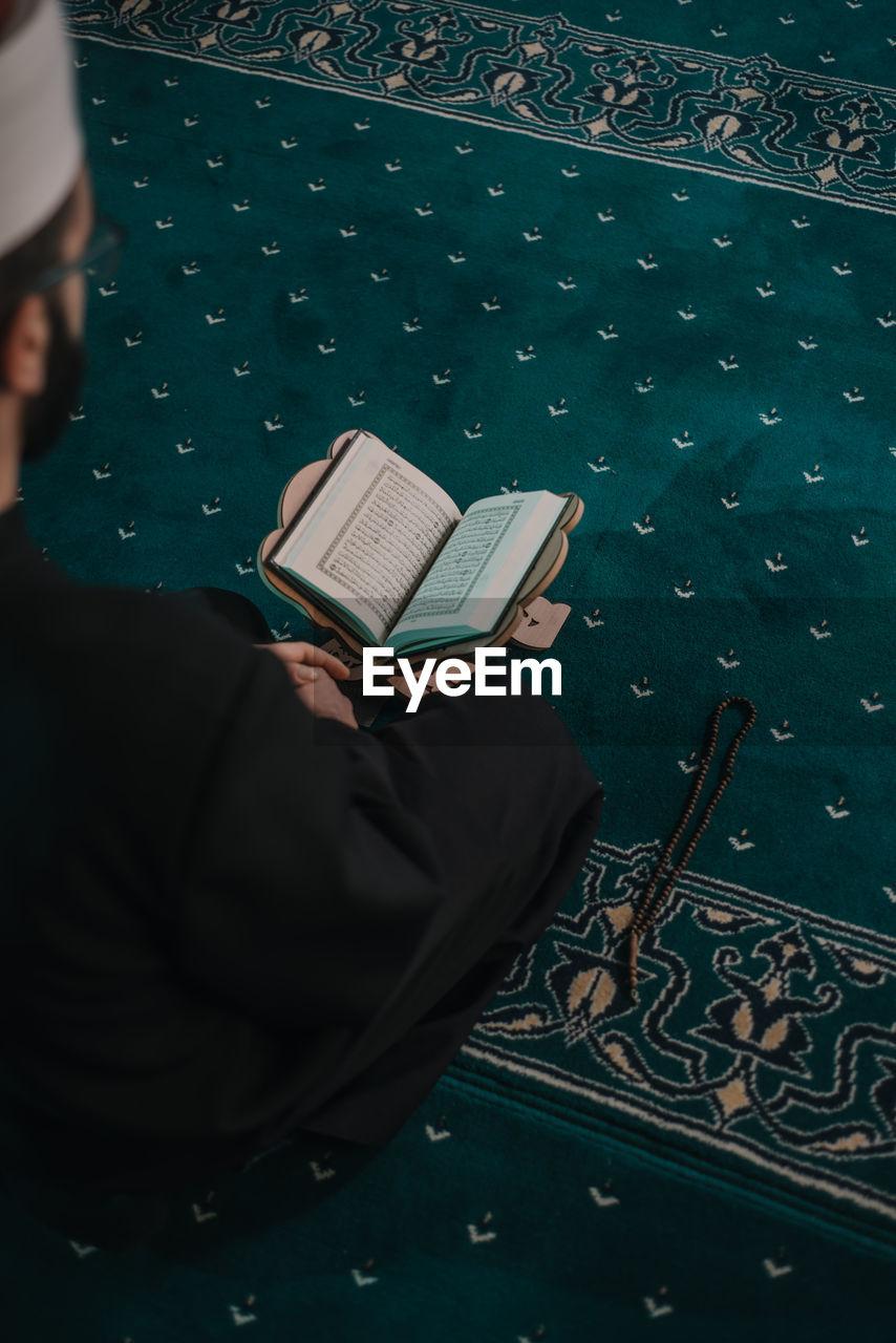 High angle view of man reading koran