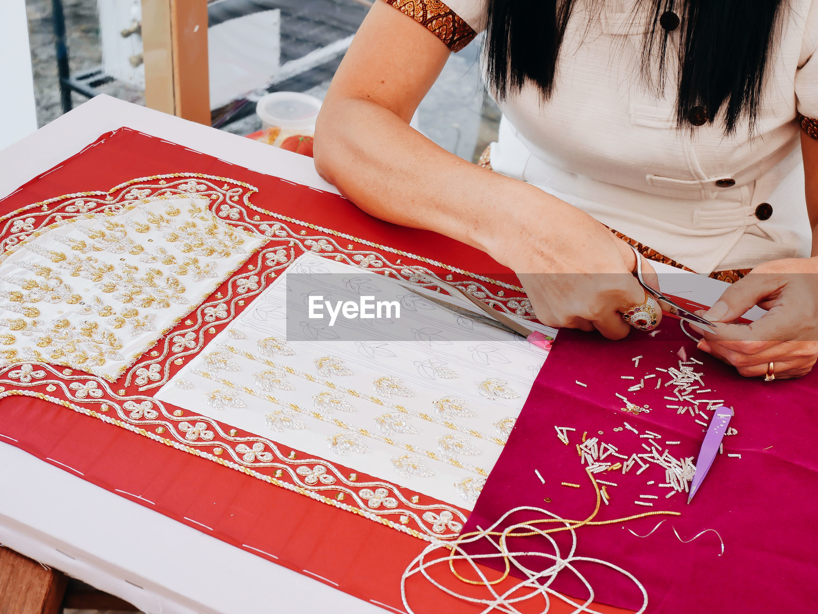 Midsection of woman embroidering jewelry