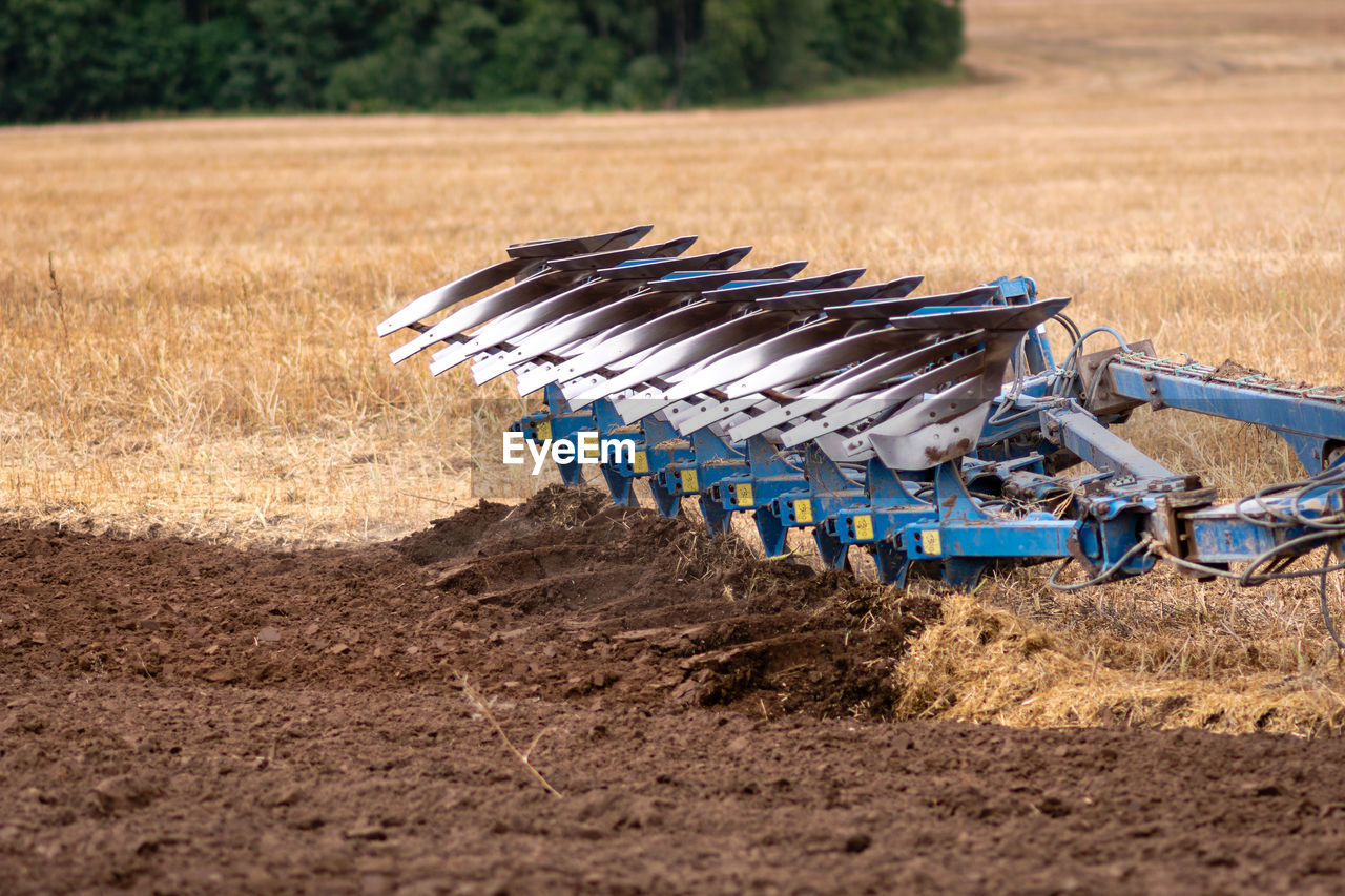 field, land, agriculture, metal, no people, landscape, nature, outdoors, day, machinery, environment, dirt, rural scene, in a row, sunlight, agricultural machinery, focus on foreground, farm, high angle view, plant