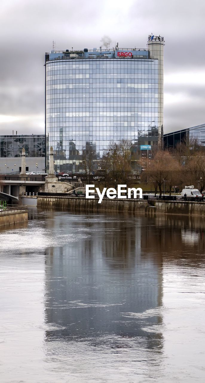 Modern Office Building Reflection In River Against Cloudy Sky