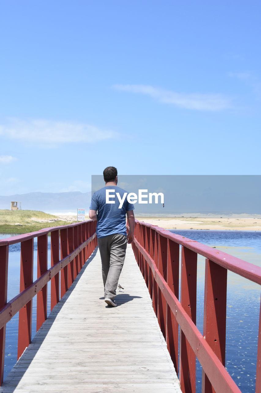 Rear view of man walking on footbridge against sky
