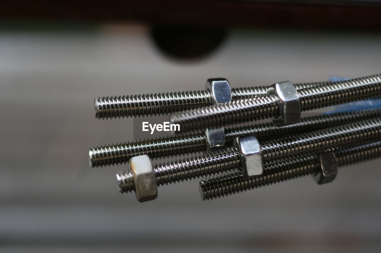 close-up, selective focus, metal, no people, bolt, screw, still life, indoors, table, focus on foreground, nut - fastener, equipment, shiny, silver colored, high angle view, work tool, pattern, reflection, shape, security