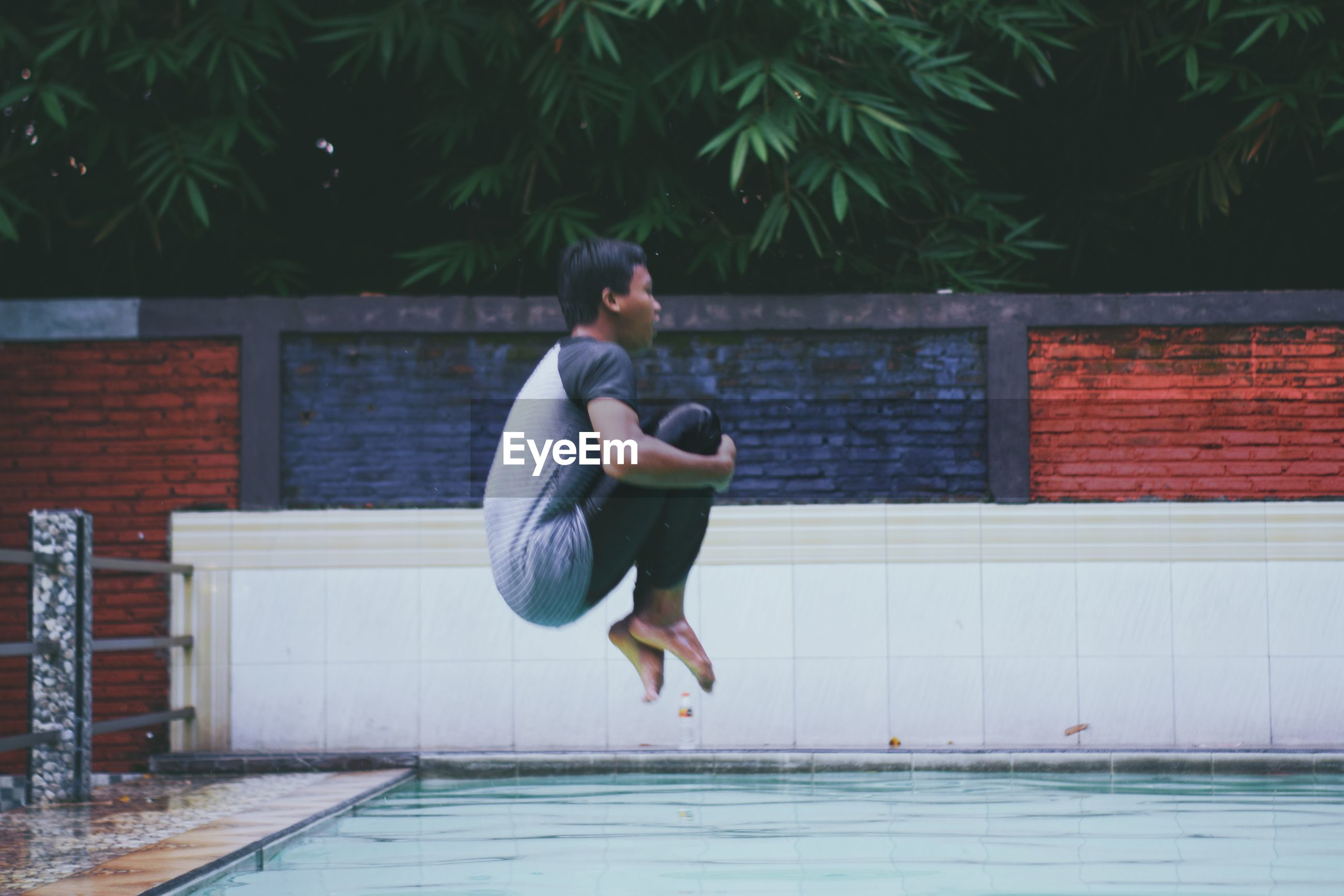 SIDE VIEW OF A MAN JUMPING IN SWIMMING POOL