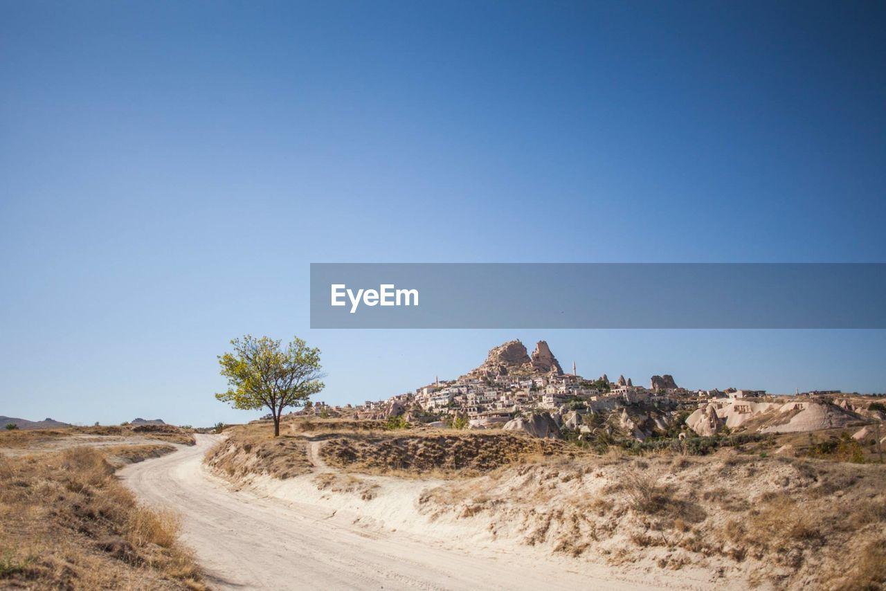 Dirt Road In Desert Against Clear Sky