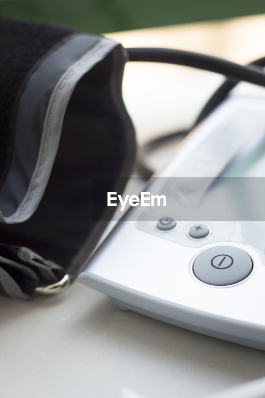 technology, close-up, still life, no people, table, indoors, connection, selective focus, communication, equipment, focus on foreground, healthcare and medicine, medical equipment, headphones, white color, high angle view, music, wireless technology, listening, black color, electrical equipment