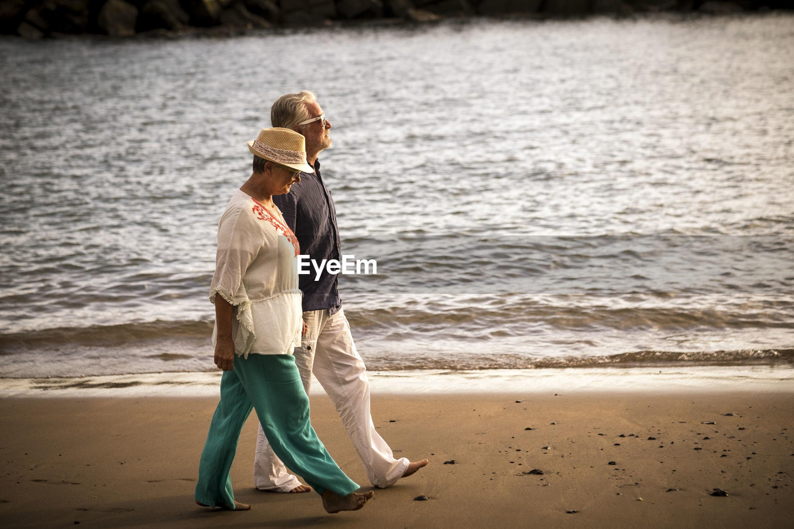 Full length of senior couple walking on shore at beach