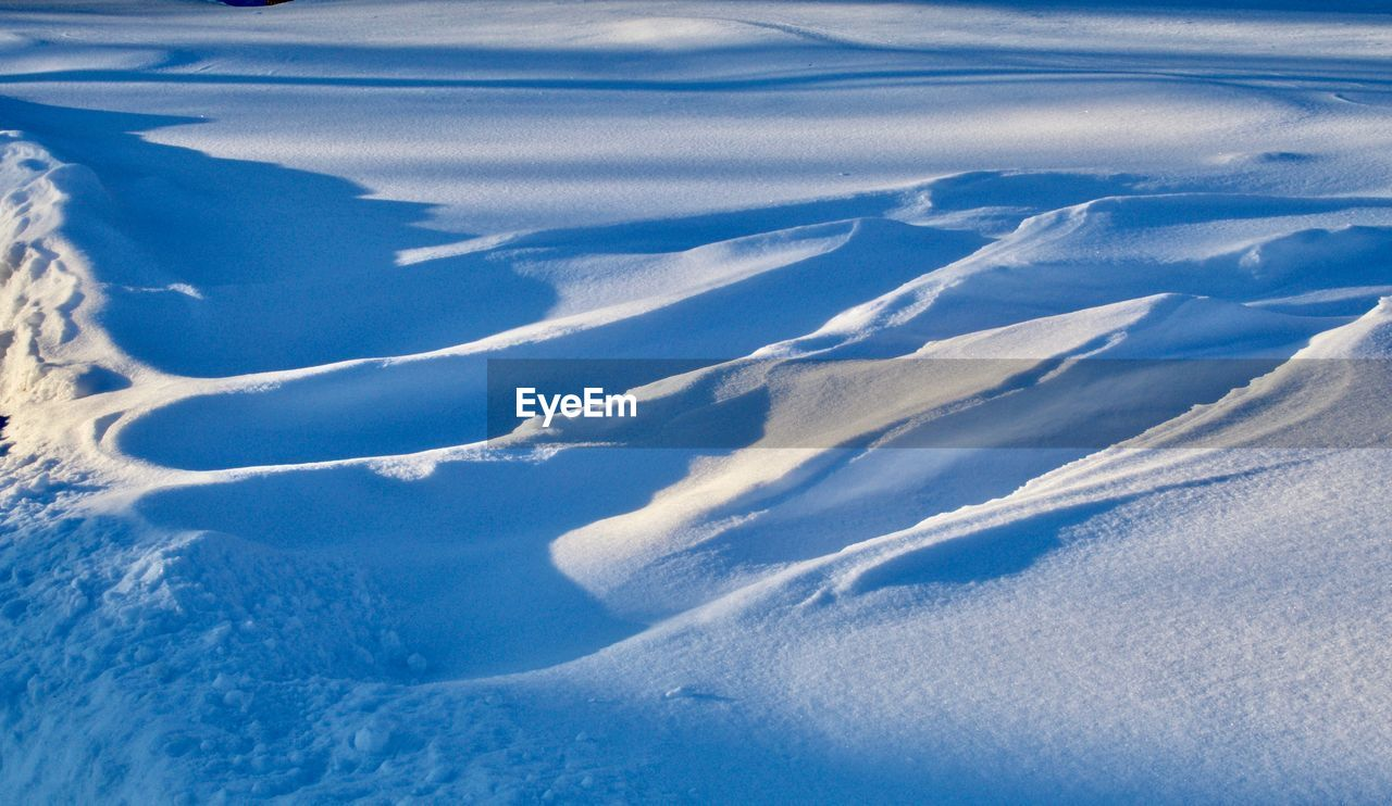 AERIAL VIEW OF SNOW COVERED LAND AND SNOWCAPPED MOUNTAINS