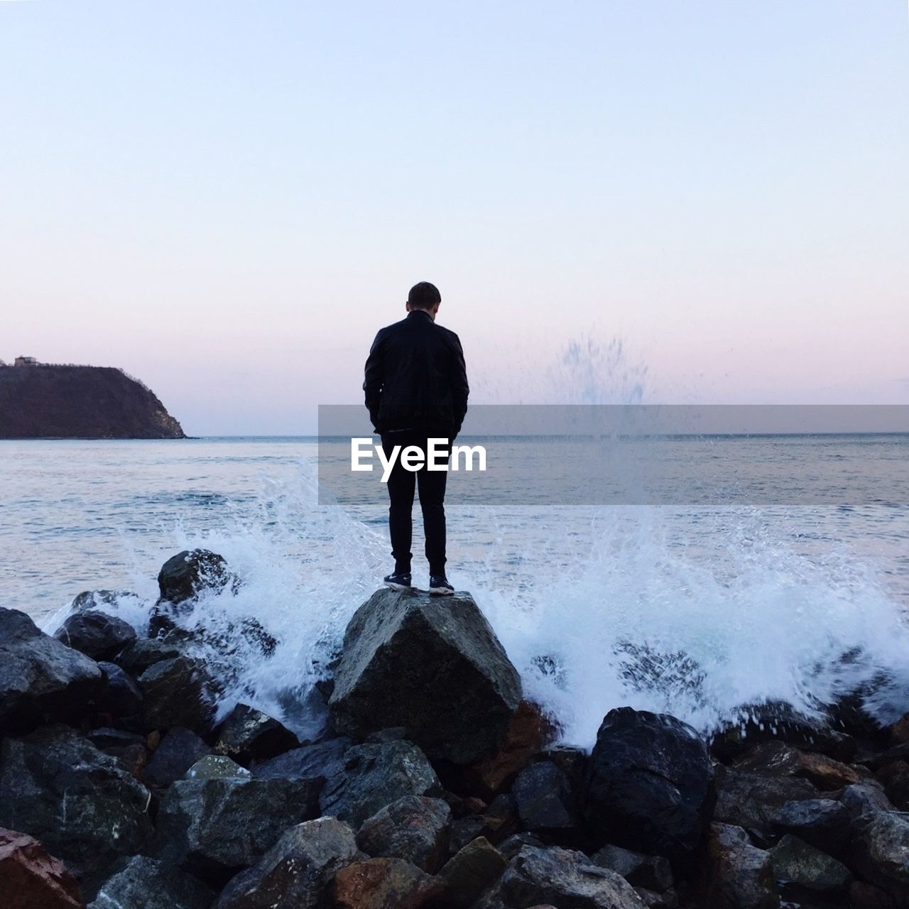 REAR VIEW OF MAN LOOKING AT BREAKING WAVE