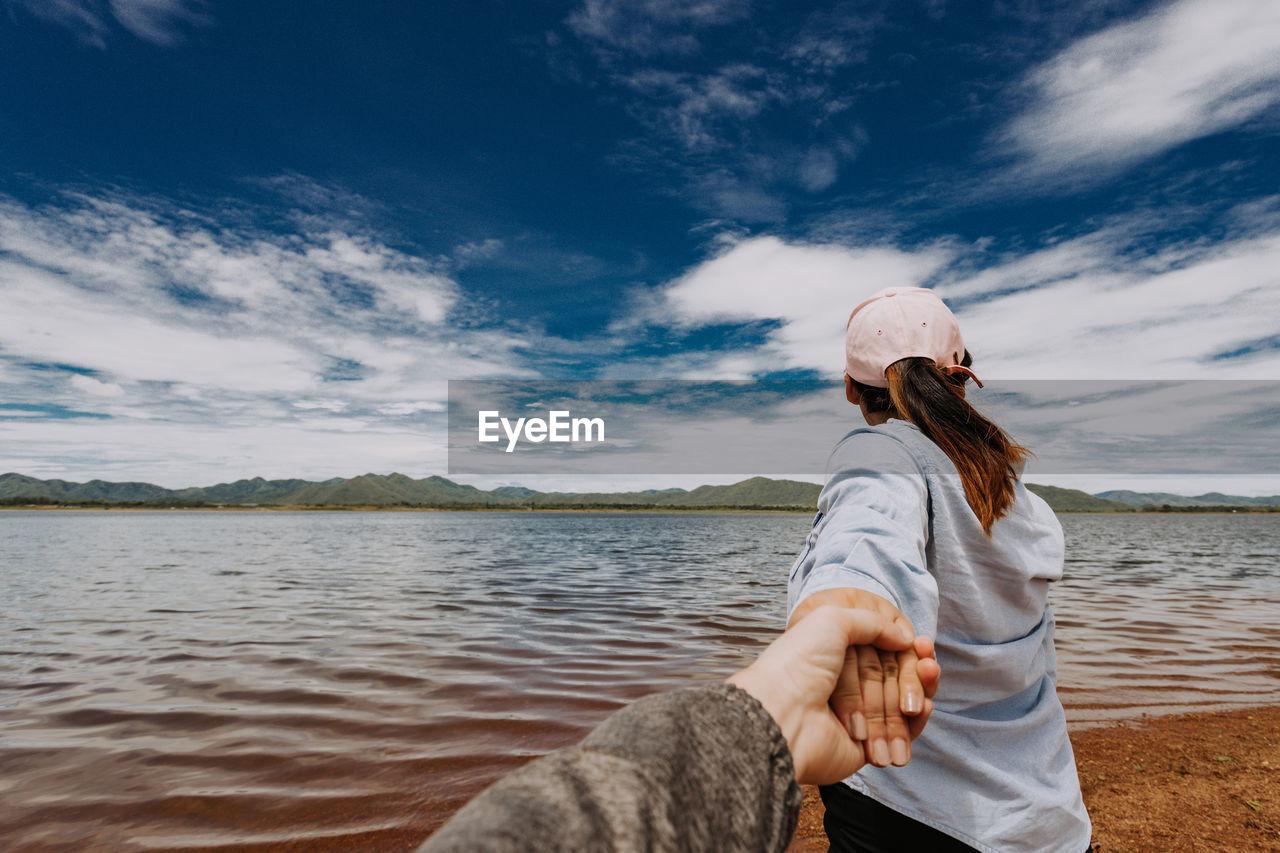 Woman holding boyfriend hand at beach against sky
