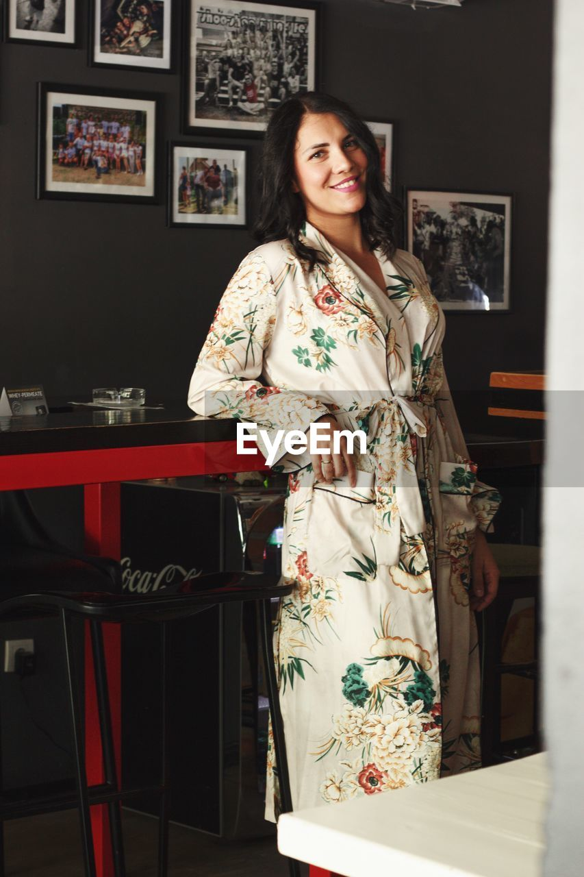 standing, one person, women, indoors, real people, lifestyles, smiling, clothing, looking at camera, adult, beauty, young adult, leisure activity, young women, home interior, beautiful woman, casual clothing, three quarter length, emotion, floral pattern, hairstyle