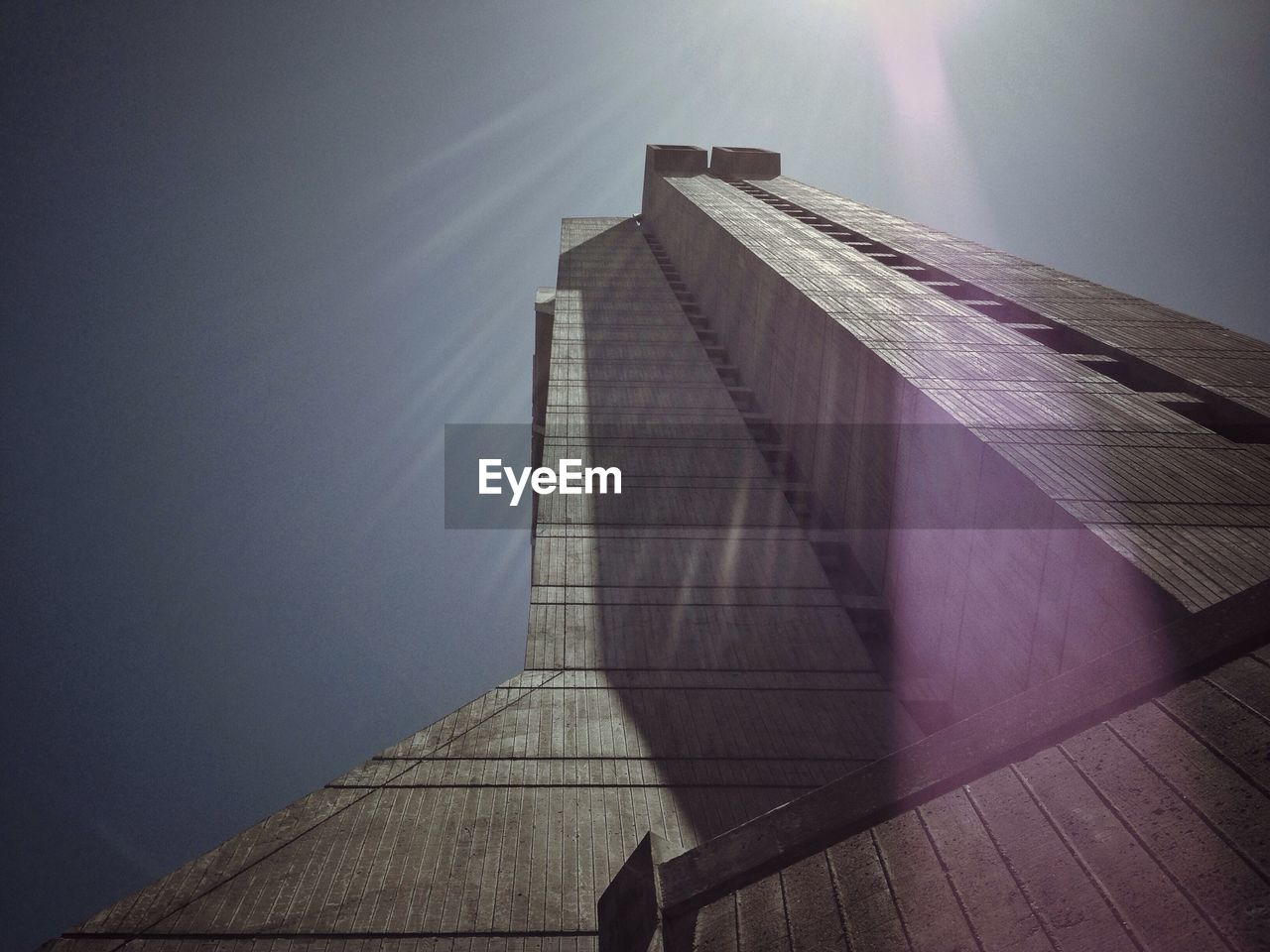Low angle view of skyscraper against clear sky on sunny day