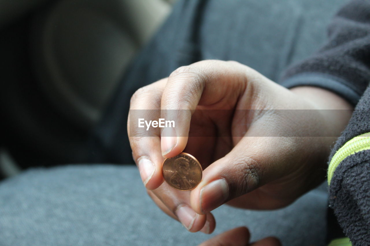 Midsection Of Person Holding Coin While Sitting Indoors