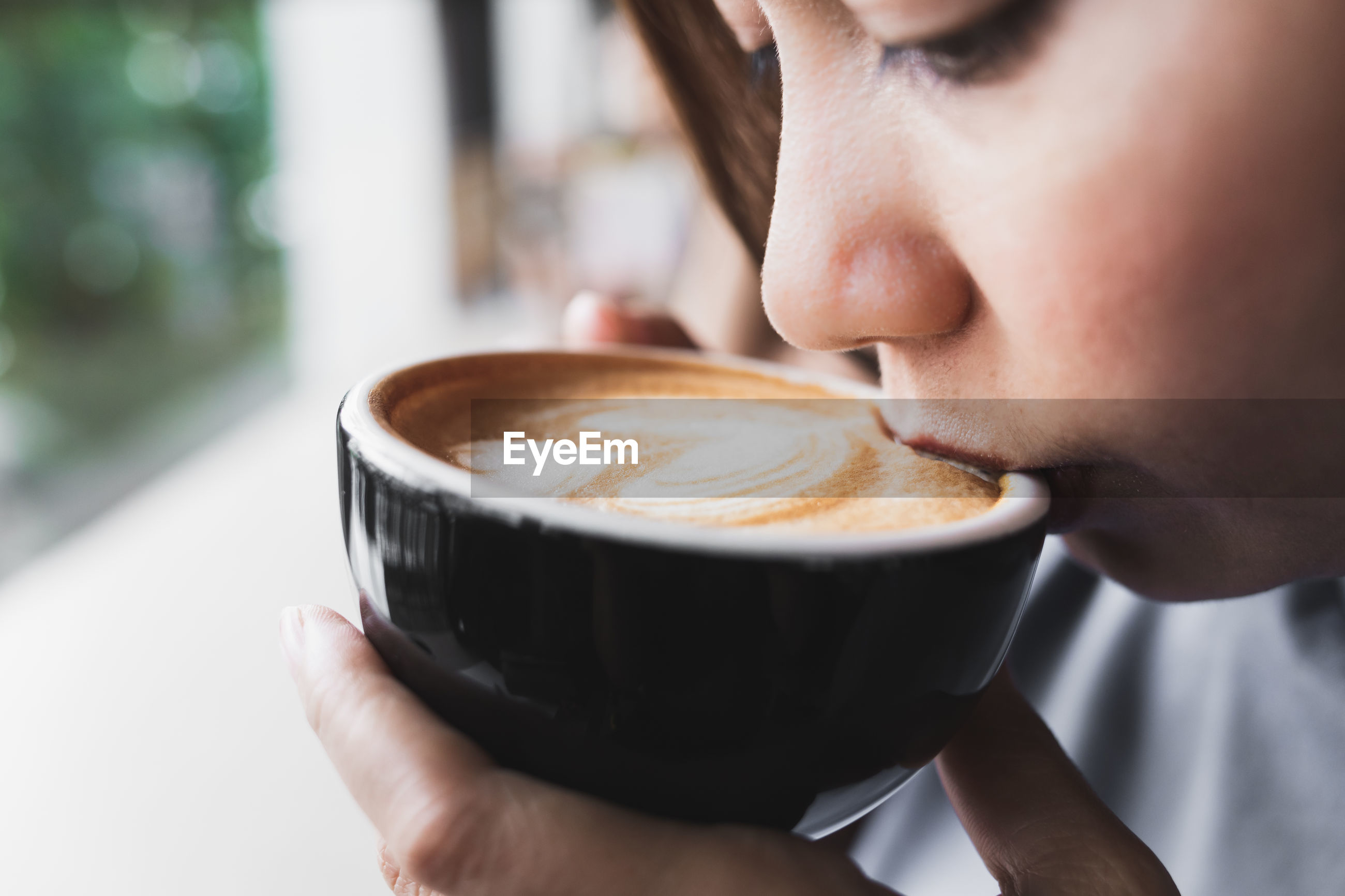 Close-up of woman drinking coffee at cafe