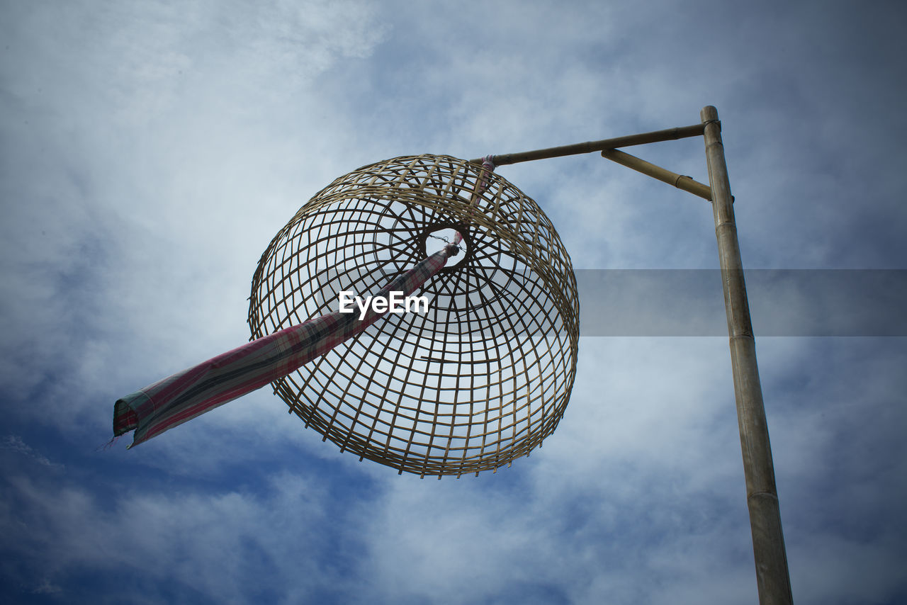 Low angle view of basket hanging on pole against sky