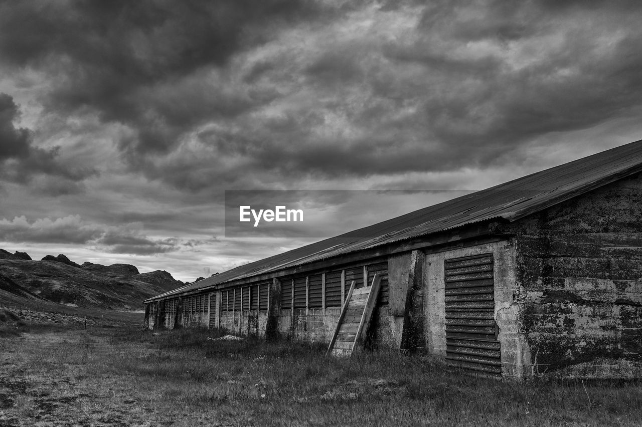 ABANDONED BUILDING ON FIELD AGAINST CLOUDY SKY