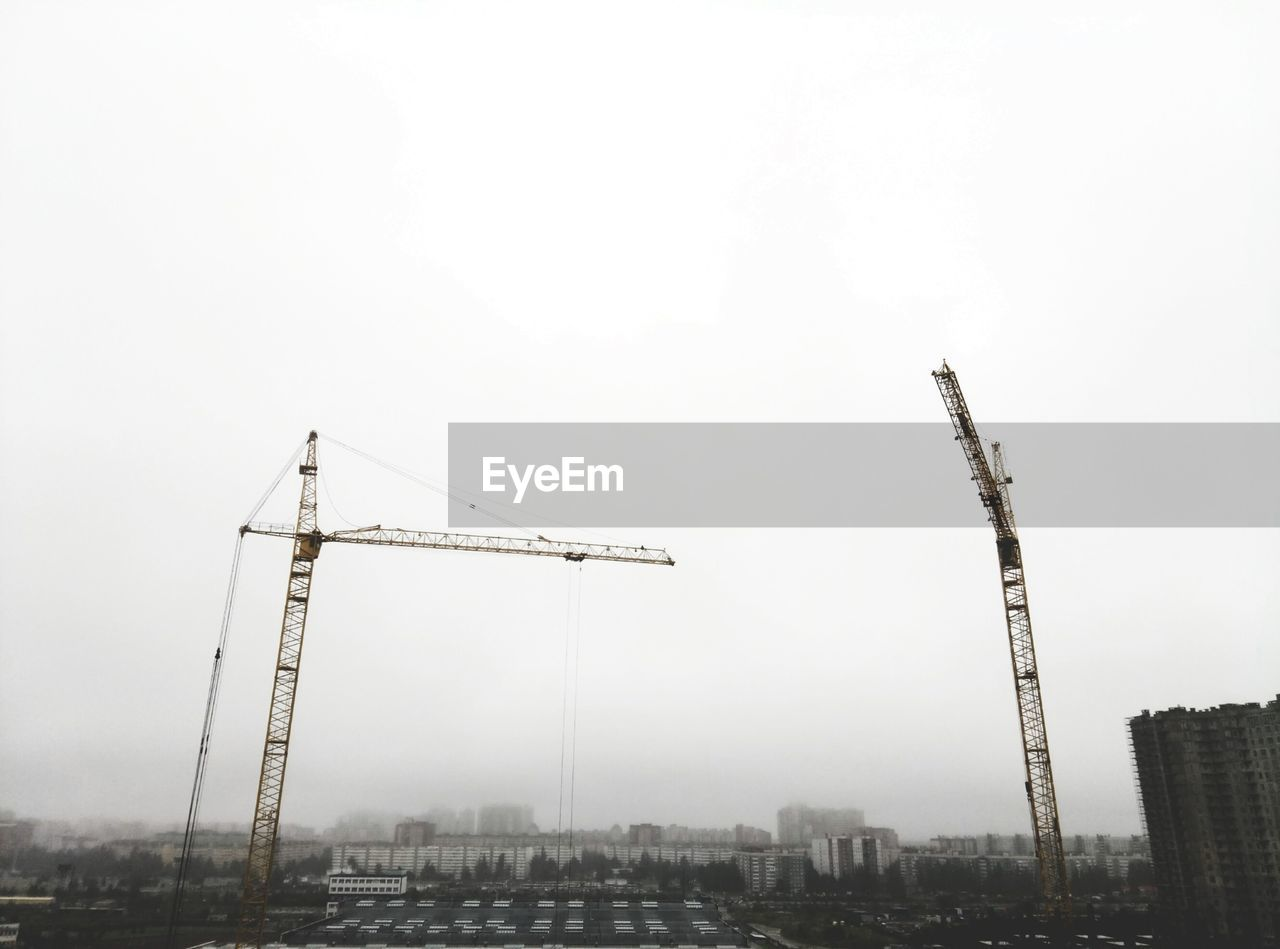 sky, crane - construction machinery, development, architecture, construction site, machinery, construction industry, building exterior, built structure, industry, nature, no people, construction equipment, incomplete, copy space, crane, city, day, fog, outdoors, cityscape