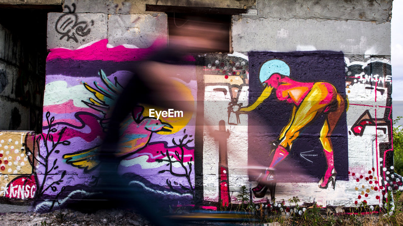 graffiti, art and craft, creativity, two people, real people, men, architecture, multi colored, street art, adult, day, people, building exterior, city, built structure, women, clothing, motion, wall - building feature, human representation, outdoors, mural