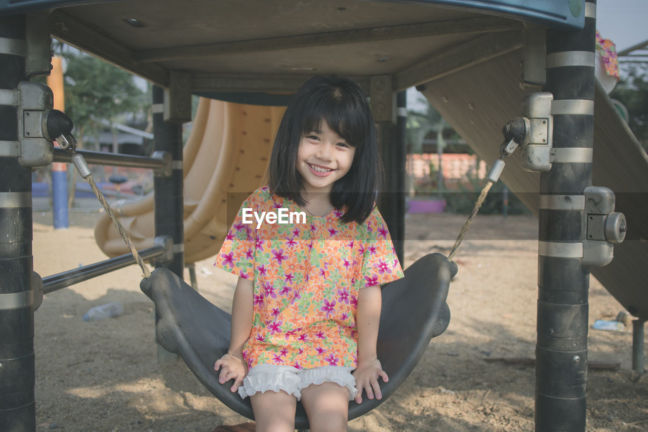 Portrait of smiling cute girl sitting on swing in park